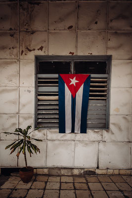 "Another example of thge many flags you will see while travelling cuba. Also a typical ""window"" as won't find many glass windows."