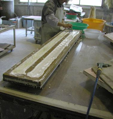型に溶かした石膏を流し込み、補強の麻糸も入れる