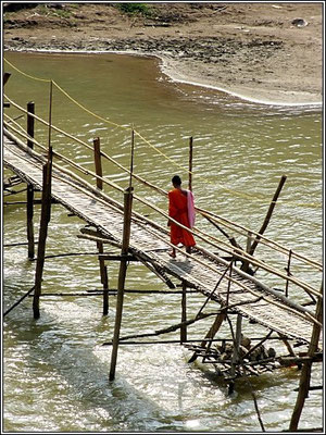 Luang Prabang -  Monk walk over a wooden  bridge