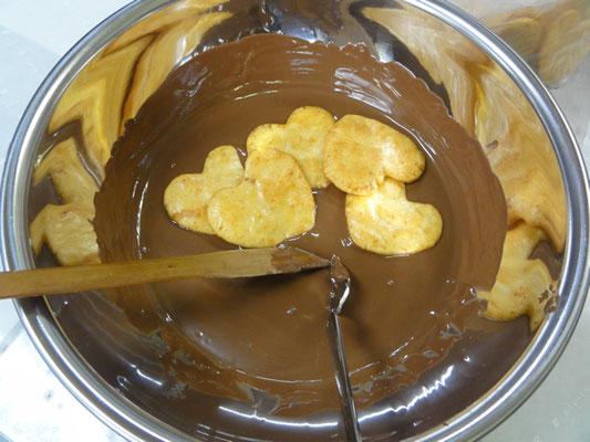 溶けたチョコレートを、一枚一枚コーティング。
