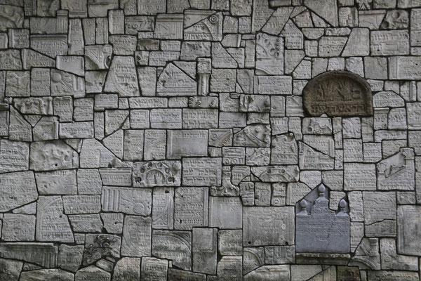Eine Mauer aus zertörten jüdischen Grabsteinen