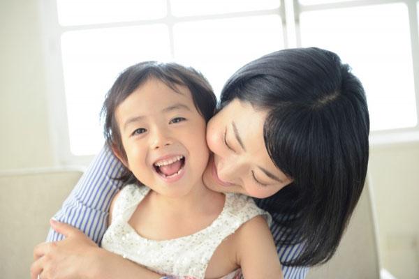 子供を後ろから抱きしめる笑顔の母親