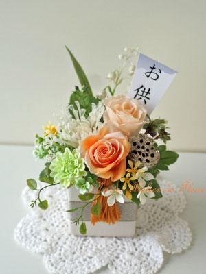 はなかすみ プリザーブドフラワーのオレンジのバラをメインに菊とアーティフィシャルフラワーを使った縦長のプリザーブドフラワーのお供えの花 高さ約18cm