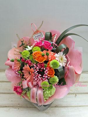 オレンジ系のガーベラやグリーンのマムの花束