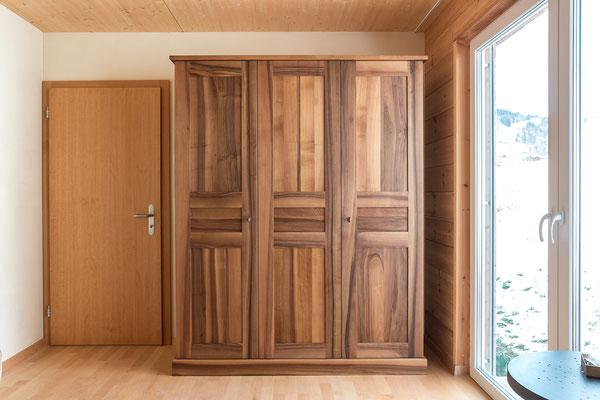 Dreitüriger Schrank aus Nussbaumholz mit gestemmten Türen und Füllungen.