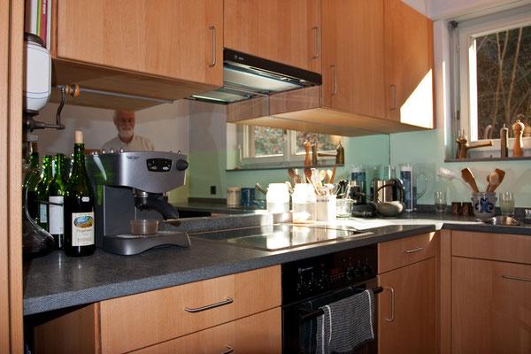 Küche aus Buche, Arbeitsfläche aus Granit, Küchenrückwand mit Spiegel.
