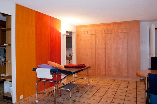 Sprechzimmer mit Schränken und farbigen Wandplatten.