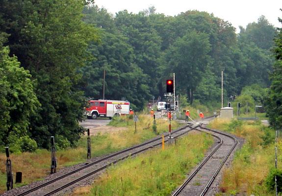 """29.06.2017: Nach Starkregen reinigt die Feuerwehr """"mit Hochdruck"""" die Spurrillen des BÜ Niederlehmer Strasse von Sand und Steinen. Zuvor war ein Triebwagen knapp der Entgleisung entgangen..."""