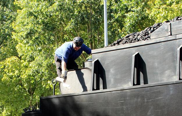 Der Lokführer kontrolliert den Wasserstand auf dem Tender der Lok