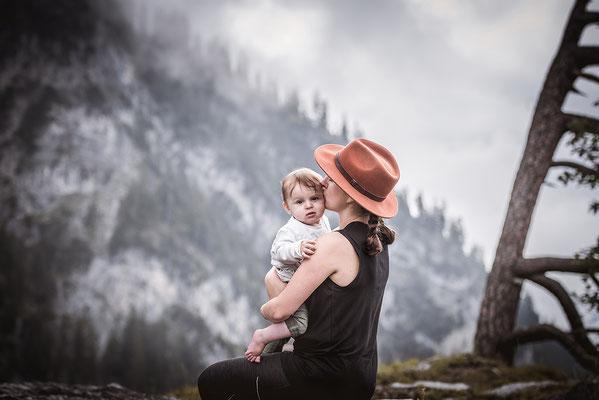 Mutter mit Kind auf dem Arm vor einer Bergkulisse festgehalten von der Familien Fotografin Monkeyjolie