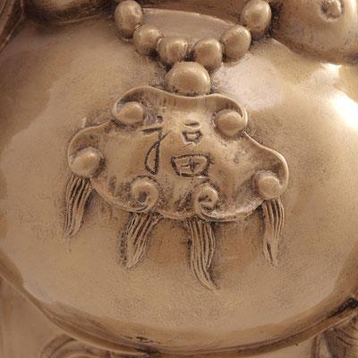 """Lachender Buddha mit Glücks-Amulett """"Fú"""" um seinen Hals. Seinen Bauch zu streicheln bringt Glück."""