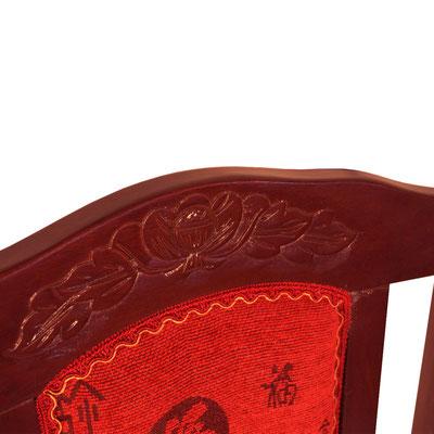 Rückenlehne mit Blumenmuster als Verzierung und mit roten Rückenkissen.
