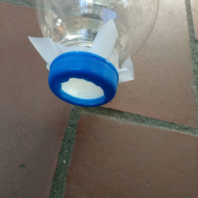 Ein Loch in den Deckel schneiden und damit den Kunststofffilter an die Flasche schrauben