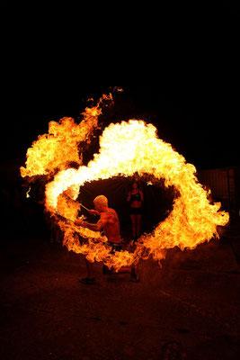 Veranstaltungsfotograf bei einer Feuershow, Eventfoto zeigt Mann mit Feuerkreis