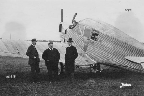 """Pilot Hesse in der F 13 """"Annelise"""". Vor dem Flugzeug der Leiter der Forschungsanstalt """"Prof. Junkers"""" Otto Mader, der Amerikaner Hesse und der Konstrukteur der F 13 Otto Reuter."""