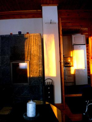 """... oder natürlich entspannt im Wohnzimmer. Das Feuer des Kaminofens wartet schon. Draußen zaubert unterdessen die Sonne eine roten Abendhimmel und """"läutet"""" den gemütlichen Teil des Abends ein."""