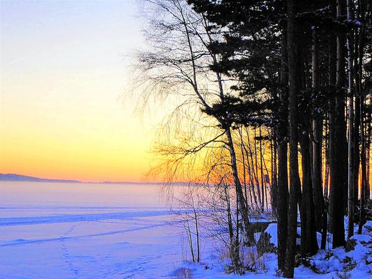 Sowohl aus der dampfenden Außensauna heraus, als auch, wie hier, direkt am Ufer des See oder aus dem Eisloch können Sie beim Saunabaden das Abendrot genießen.