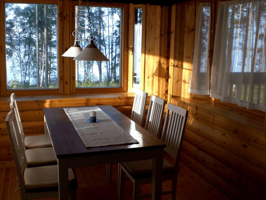 Dining room with sunny jutty in the kitchen. Breakfast in the morning sun. View onto the lake