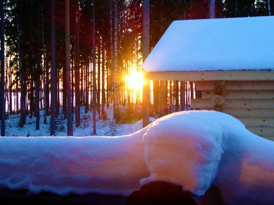 Hinein in die dampfende Sauna beim Abendrot und flackernden Feuer des großen Saunaofens.  Und dann Abkühlung im selbst gesägten Eisloch finden.