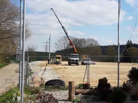 Die neuen Flutlichtmasten werden in Fundamente gehoben