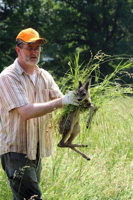 Mit Handschuhen und Grasbett: ein Jäger rettet ein Kitz aus einer Wiese. Quelle: DJV