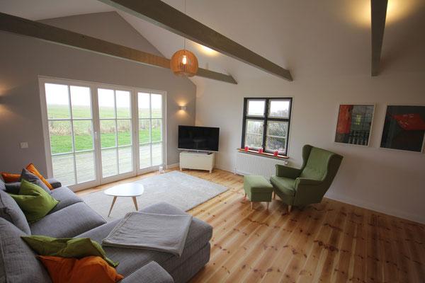 Das Wohnzimmer vom Seegut im lichtdurchfluteten Anbau mit alten Holzbalken