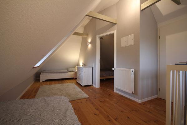 Im Obergeschoss ist Platz für vier Personen: in einem Doppelbett und zwei Einzelbetten