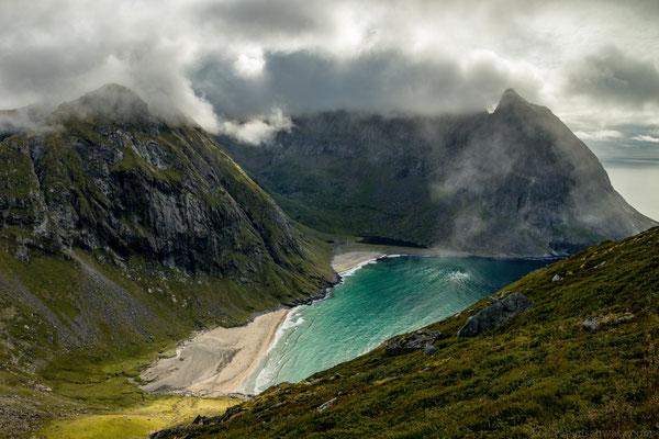 türkises Wasser und nebelverhangene Berge