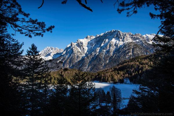 Die verschneiten Hänge des Karwendels und der zugefrorene Lautersee