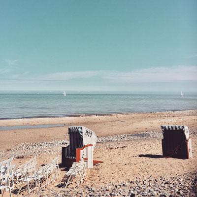 2 Strandkörbe und Klappstühle am Meer, in der Ferne sind Segelschiffe erkennbar