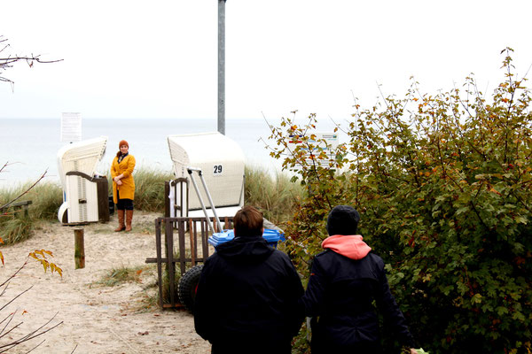 Das Hochzeitspaar geht in winterlicher Kleidung zu den Strandkörben, wo Constanze bereits auf sie wartet