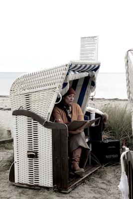 Hochzeitsrednerin bereitet sich im Strandkorb vor. Sie hält ein Notizbuch