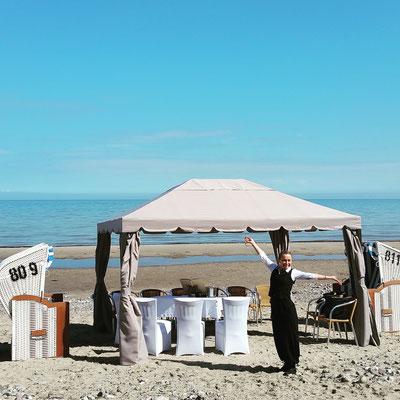 Hochzeitsrednerin am Strand in aufgeregter Pose vor 2 Strandkörben und Pavillon