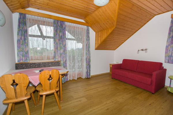 Wohnzimmer mit Essbereich. Der Teppichboden ist einem Holzboden gewichen.