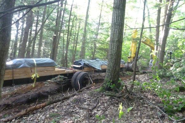 The excavator pulls the bridge components through the woods