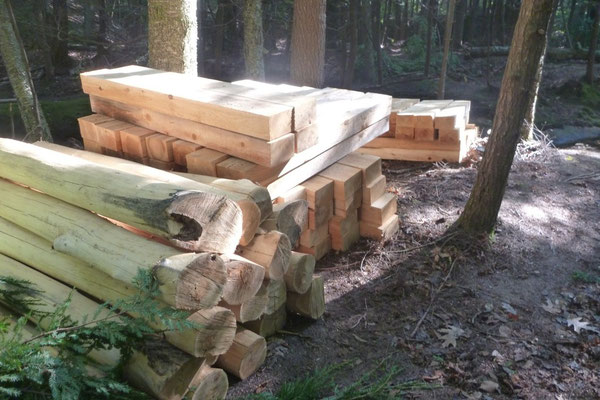 Cedar decking and locust posts are stacked for use in the bridge construction