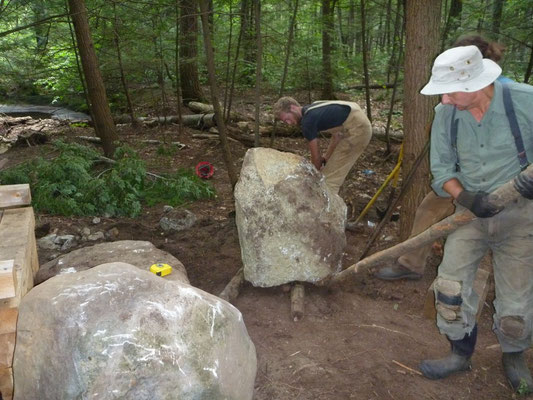 The crew moves a large step stone into place