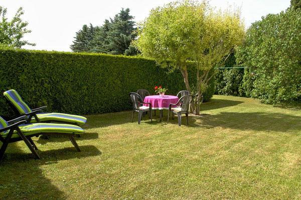 Gartenbereich vom Ferienhaus mit Tischgruppe und Liegestühlen