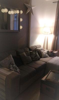 Déco salon cosy by Fannygloo : accumulation de coussins, miroir, lampadaire tamisé, guirlande lumineuse & malle ancienne