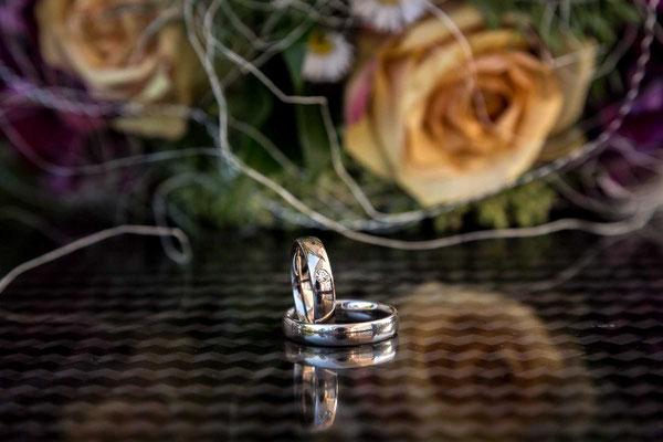 Die Ehering vor dem Brautstrauss