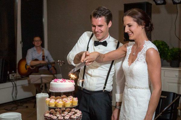 Das Brautpaar schneidet den Kuchen an