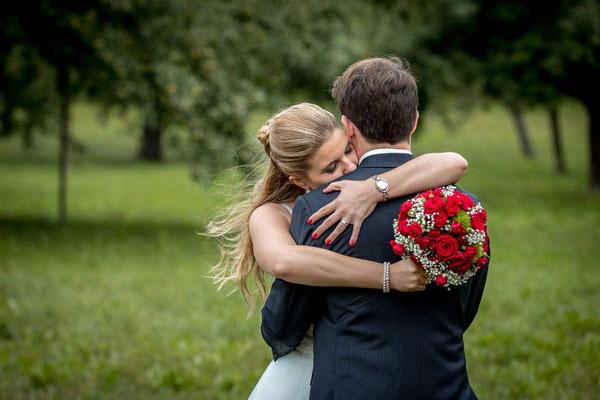 Die Braut umarmt den Bräutigam