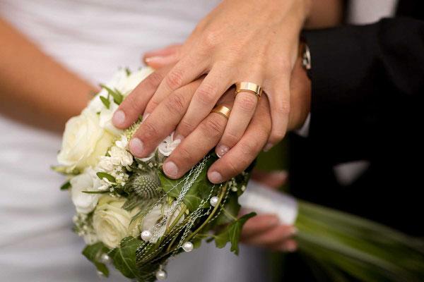 Die Eheringe mit dem Brautstrauss