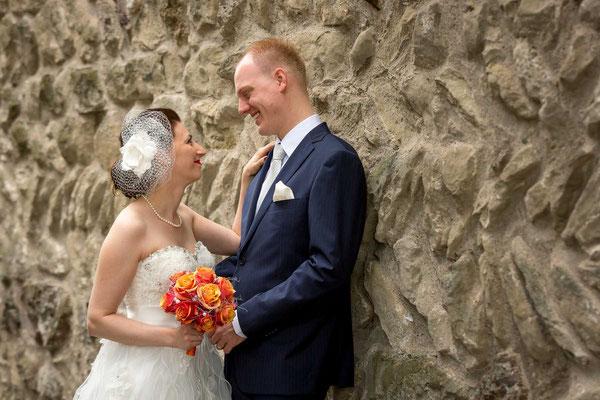 Hochzeitspaar an Mauer lehnend beim Schloss Greifensee