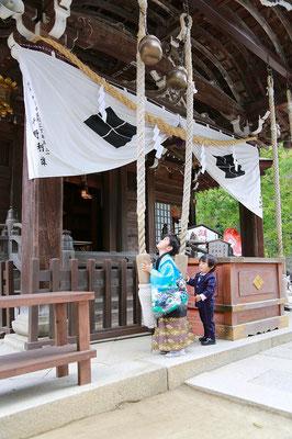 武田神社にて鈴緒を鳴らす七五三五歳男の子