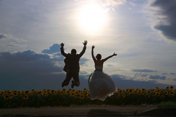 ひまわりウェディング夕日のひまわりに向かってジャンプしている新郎新婦