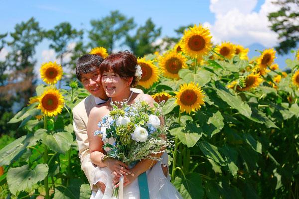ひまわりウェディング前撮りロケ撮影新婦大きなブーケをもって後ろから抱きしめる新郎の写真