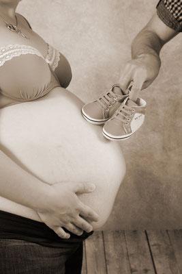 Schwangerschaftsfotografie, Papi läuft mit Babyschuhen auf Mamis Bauch