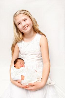 Newborn Fotoshooting, Baby schläft in den Armen der grossen Schwester, Herznach