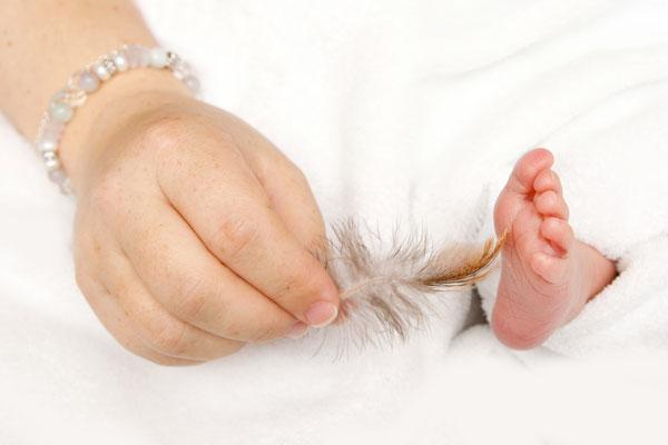 Newborn Fotoshooting, kleiner Fuss wird mit einer Feder gekitzelt, Möhlin